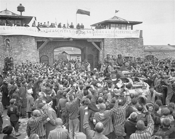 "Tanks of U.S. 11th Armored Division entering the Mauthausen concentration camp; banner in Spanish reads ""Antifascist Spaniards greet the forces of liberation"". The photo was taken on 6 May 1945"